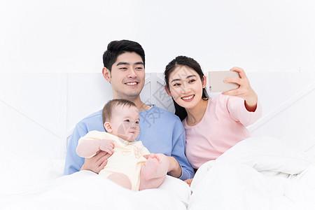 爸爸妈妈带着婴儿在床上自拍图片
