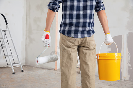 装修工人拿水桶刷子背影特写图片