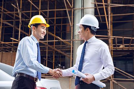 建筑工程师拿图纸握手图片