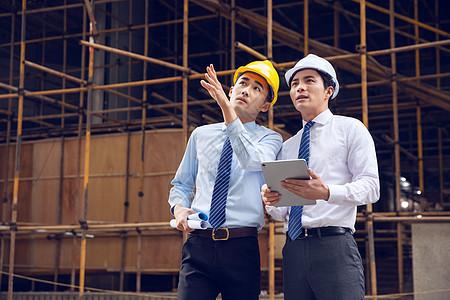 建筑工程师拿平板讨论施工项目图片