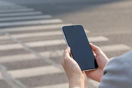 女性拿手机过人行横道局部特写图片