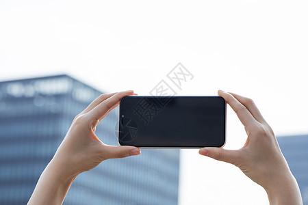 女性拿手机拍远处建筑特写图片