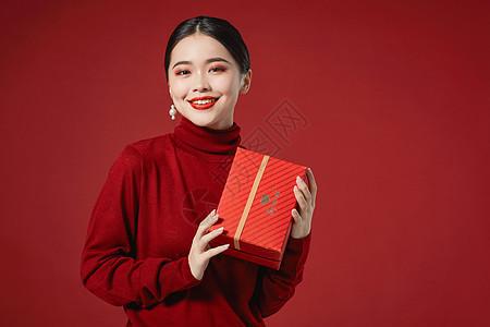 年轻美女手拿礼物盒图片