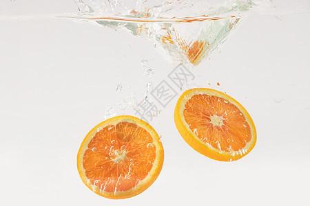 掉落水中的橙子水果切片图片