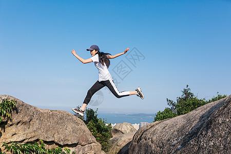 郊外石头上跳跃中的美女图片