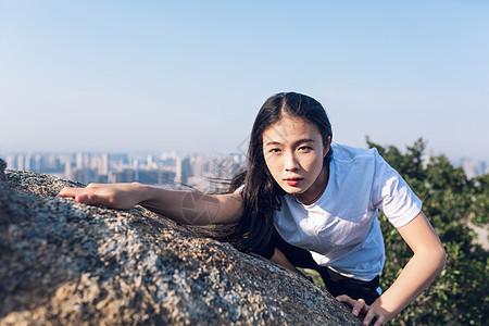 户外石头上攀岩女性图片