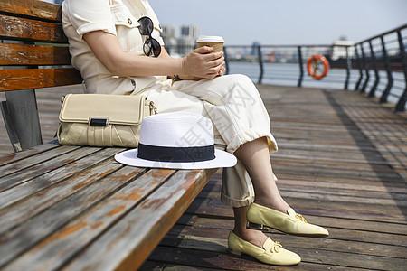 坐在江边看风景喝咖啡的时尚美女图片