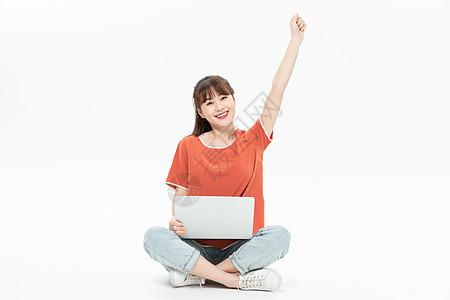 美女坐地上举手庆祝图片