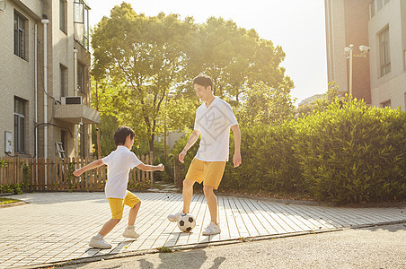 父亲陪孩子一起踢足球图片