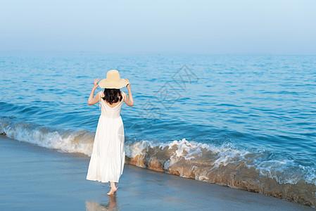 海边沙滩散步的美女背影图片