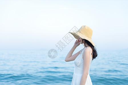 海边戴草帽的女生侧影图片