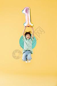 手举气球跳跃的小男孩图片