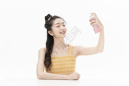 使用防晒喷雾的可爱女孩图片