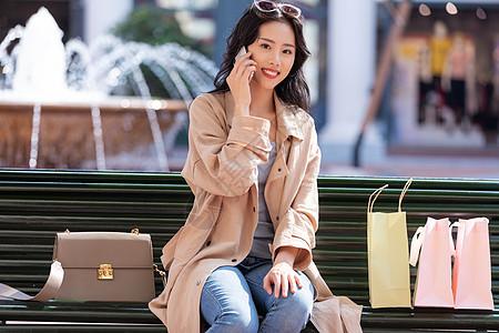 坐在椅子上打电话聊天的青年女性图片