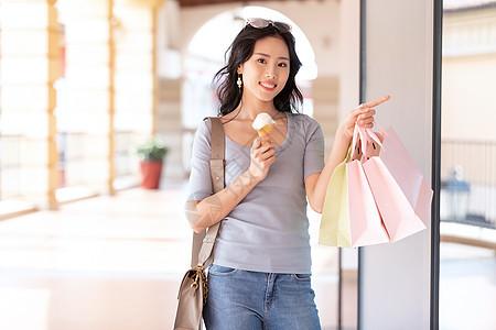吃冰淇淋逛街的女性图片