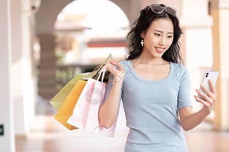 拎着购物袋打电话聊天的女性图片