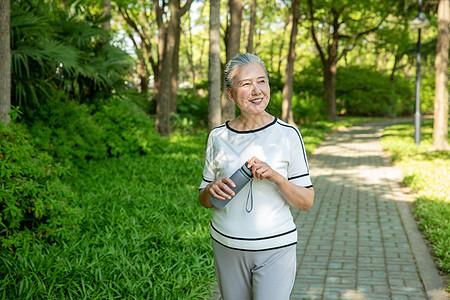 老年女性户外散步喝水图片