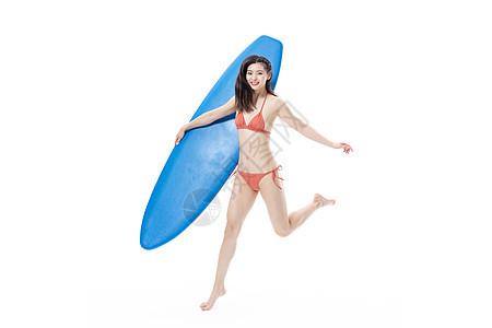 夏日泳装女性玩冲浪板图片