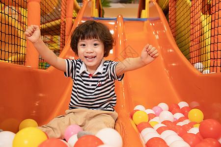 小男孩游乐园玩滑滑梯图片