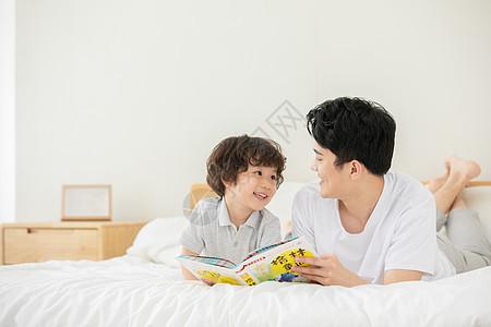 父子躺床上看童话故事书图片