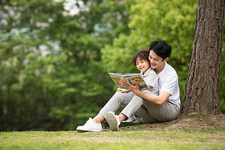 父子在公园里看童话故事书图片