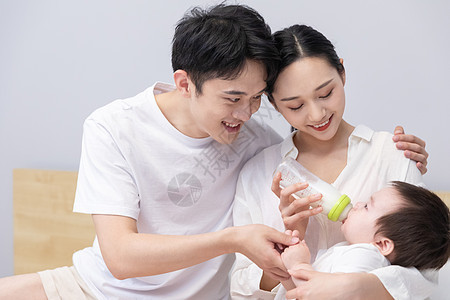 一家三口爸爸妈妈喂婴儿喝奶图片