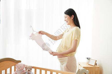 孕妇拿着宝宝衣服图片