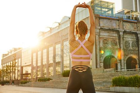 运动美女晨练热身拉伸背影图片
