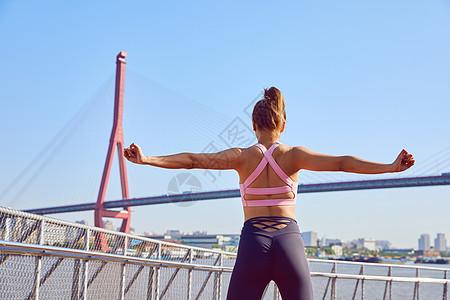 运动女性伸展手臂热身背影图片