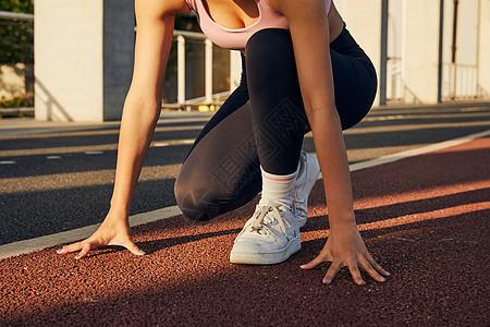 运动女性起跑准备动作特写图片