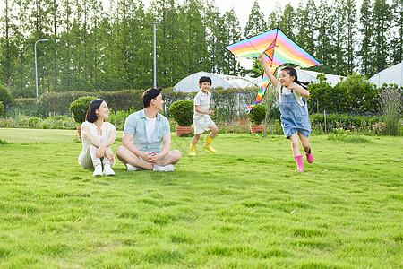 年轻夫妻看着孩子追逐玩风筝图片