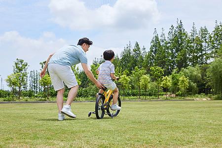 爸爸陪伴小男孩骑自行车背影图片