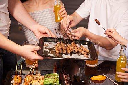 青年朋友聚会吃烤串特写图片