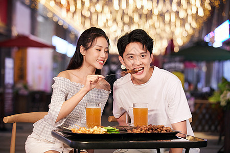 青年情侣夜市吃烤串图片