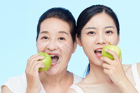 年轻美女和中年女士一起咬苹果动作图片