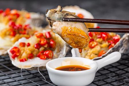 筷子夹起肥美的生蚝肉蘸料图片