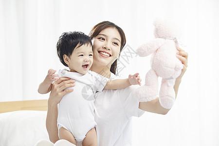 年轻妈妈用毛绒玩具逗宝宝开心图片