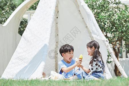 小男孩和小女孩坐在草坪上吃冰淇淋图片