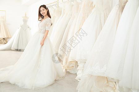 在婚纱店试穿婚纱的甜美女孩图片