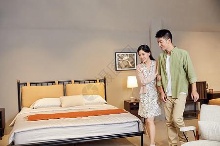 年轻夫妻逛家居店选购双人床图片