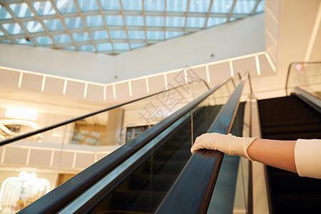 戴防护手套乘坐商场扶梯特写图片