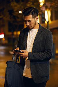 熬夜加班的商务男士低头玩手机图片