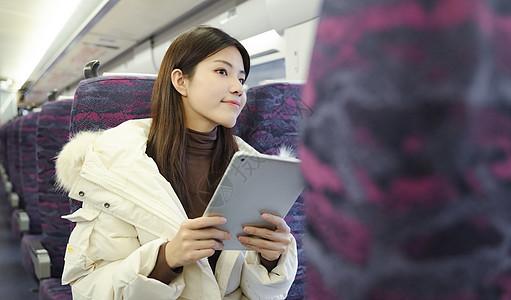 女生在火车上拿着平板电脑看窗外风景图片