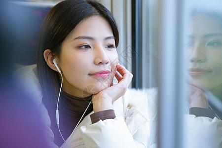 坐在火车上戴着耳机看窗外风景的女性图片