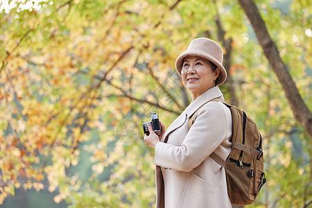 秋天老人逛公园拿相机拍摄秋季风景图片