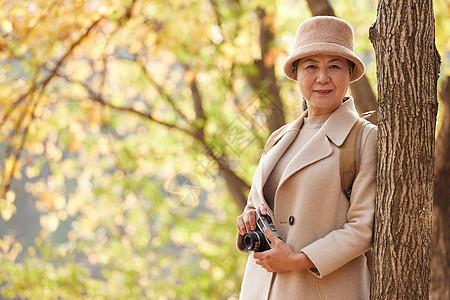 老人逛公园旅游拿相机拍摄秋季风景图片