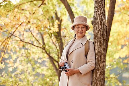 老人逛公园拿相机拍摄秋季风景图片
