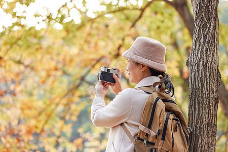 安逸老人逛公园拿相机拍摄秋季风景图片