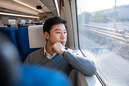 乘坐火车的男性看窗外风景图片