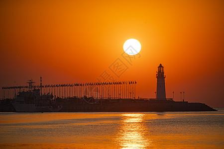 日出时红彤彤的海和伫立的灯塔图片